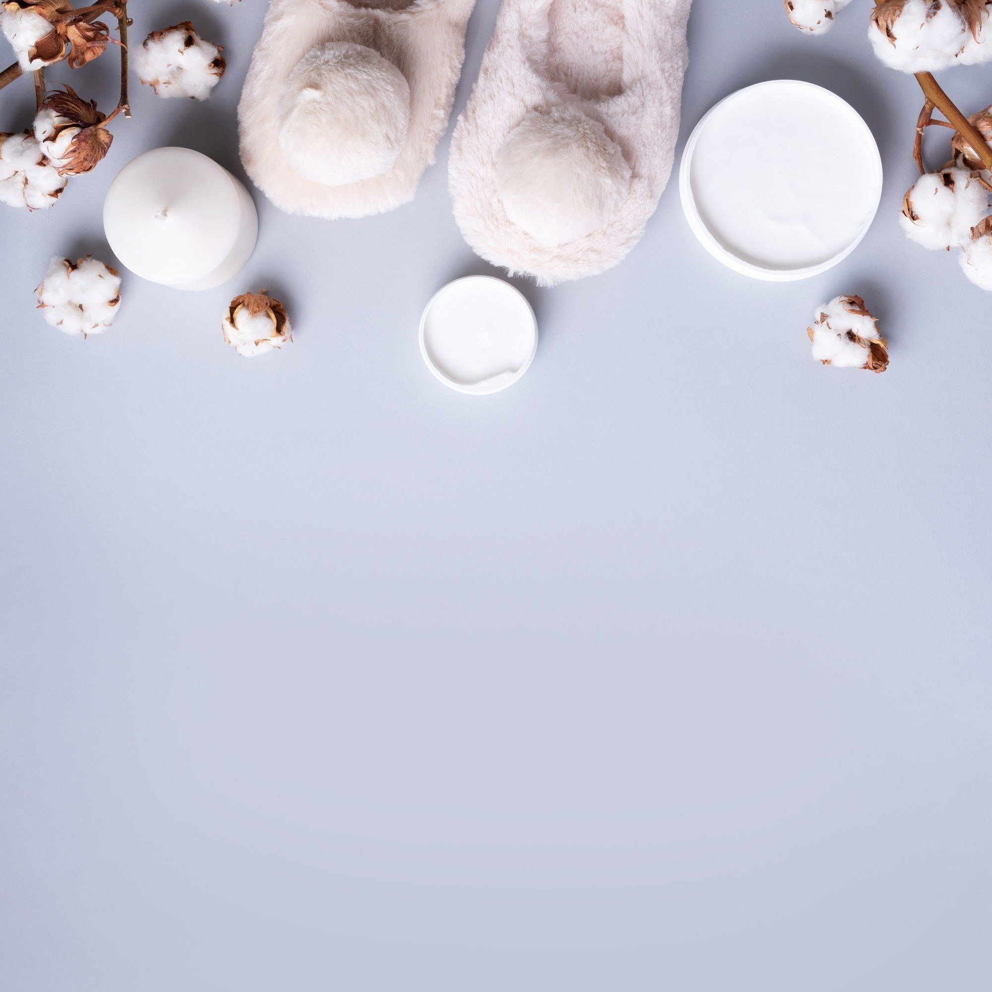 Bathroom accessories, nude fluffy home slippers, cotton flowers, candle, skin care products on grey
