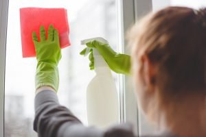 Women cleaning a window with spray and cloth. Close up